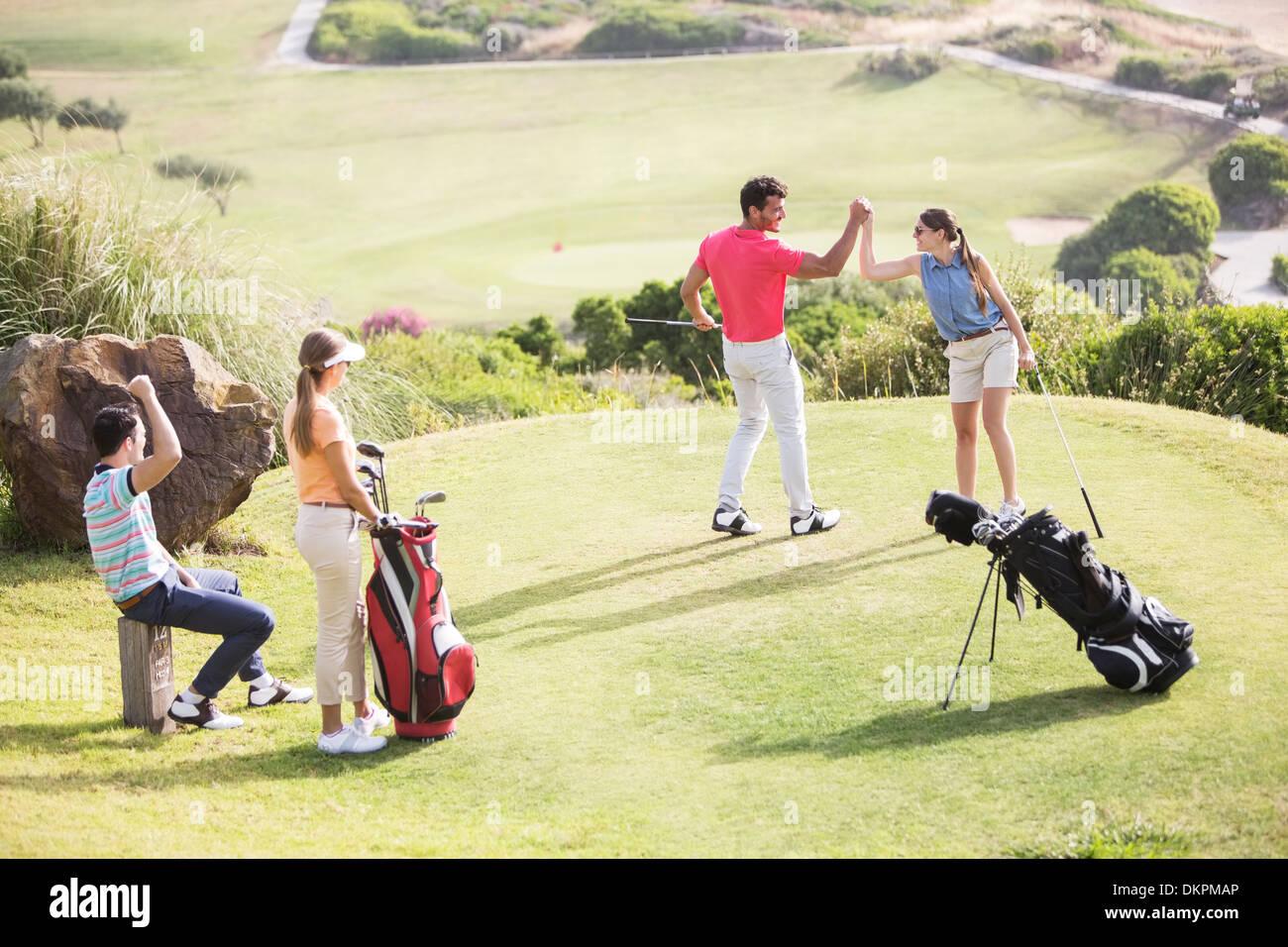 Les amis en jouant au golf sur le cours Photo Stock
