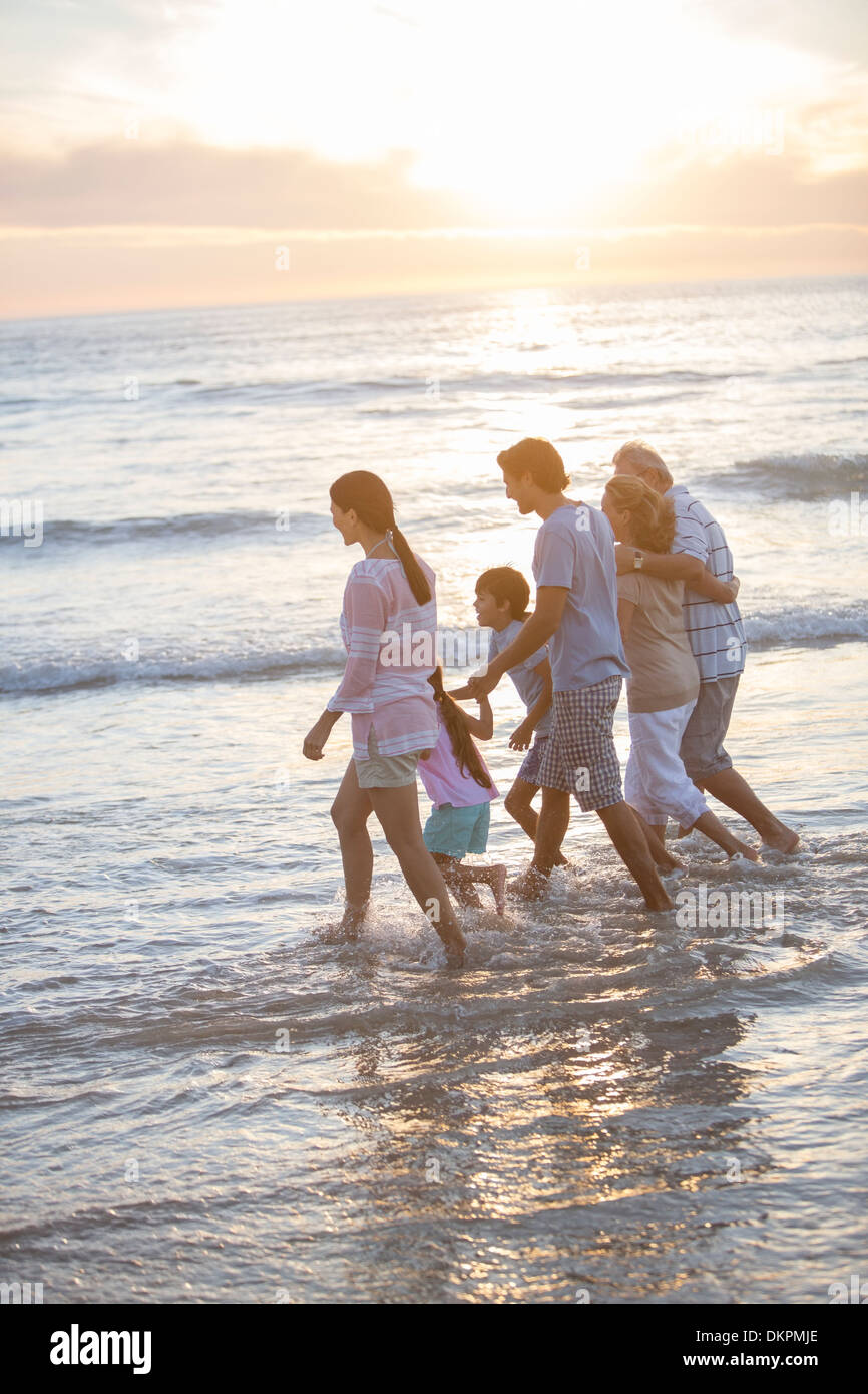 Multi-generation family walking in surf at beach Photo Stock