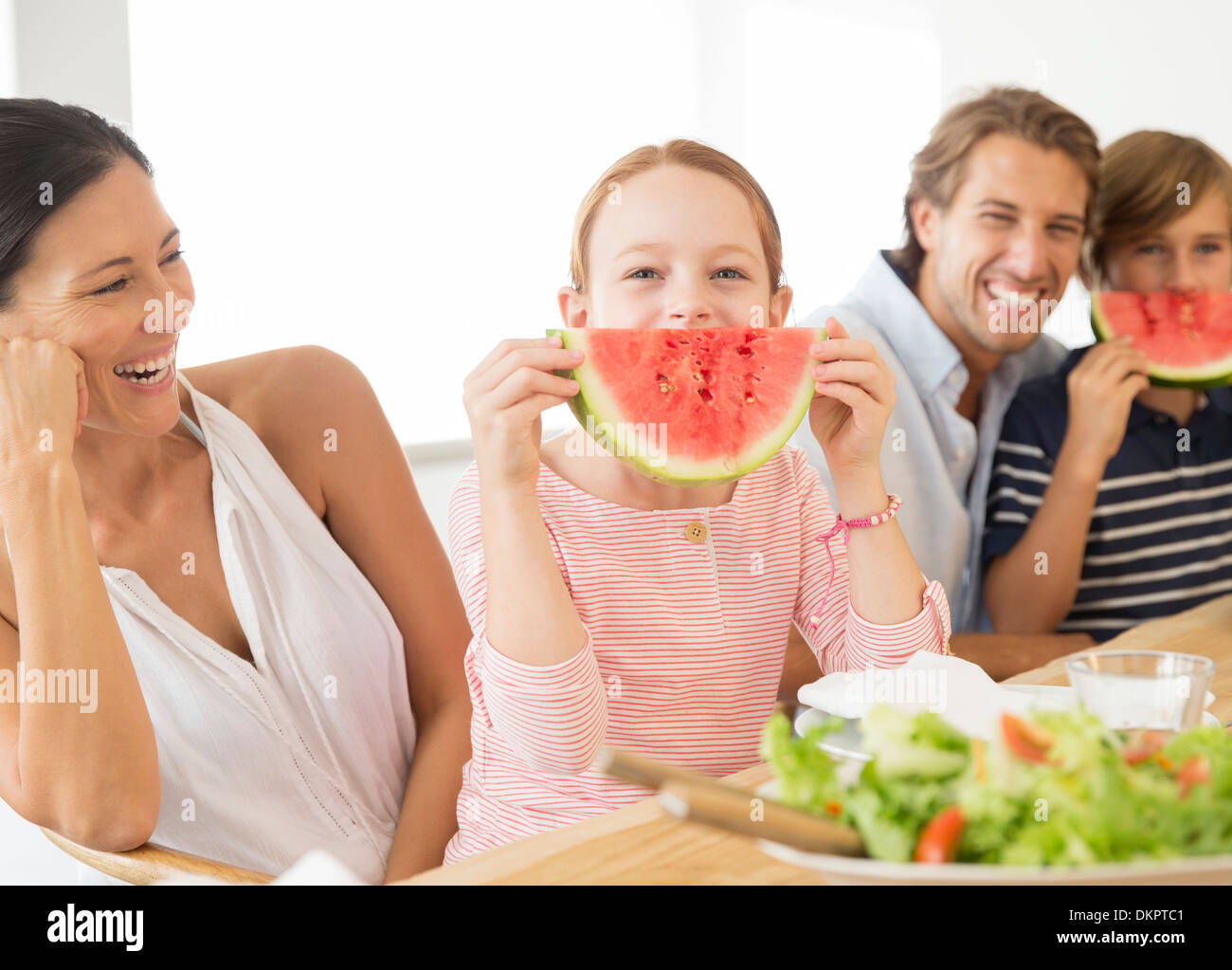 Family eating watermelon at table Photo Stock