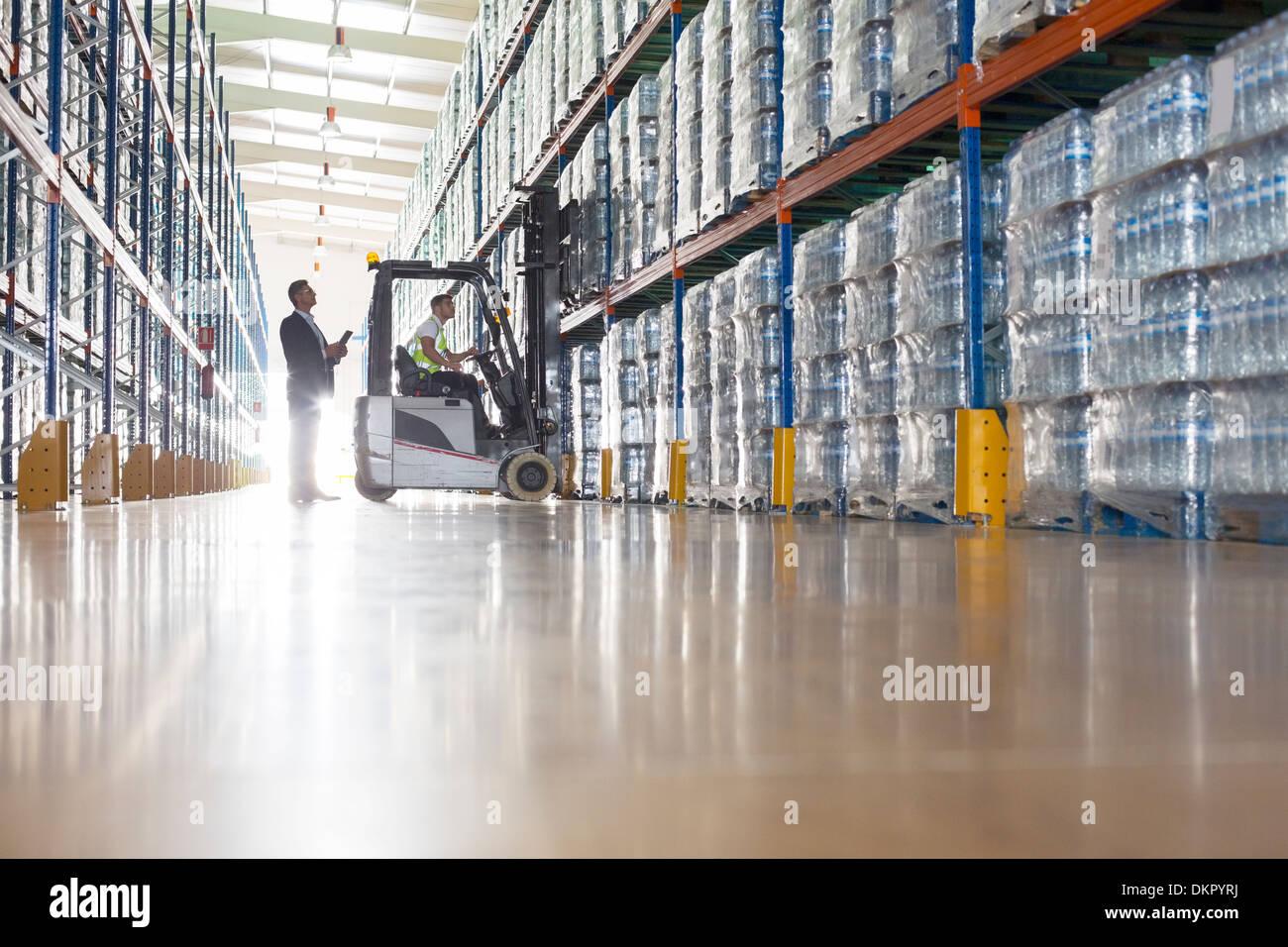 Avec les travailleurs d'entrepôt dans l'embouteillage de chariot élévateur Photo Stock