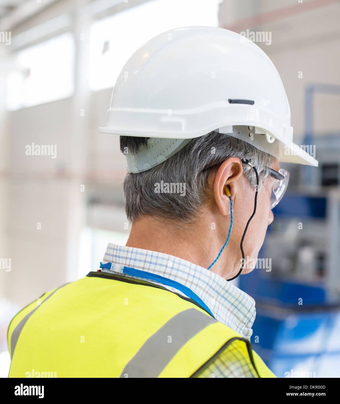 Worker wearing hard hat et bouchons d'oreilles. Photo Stock