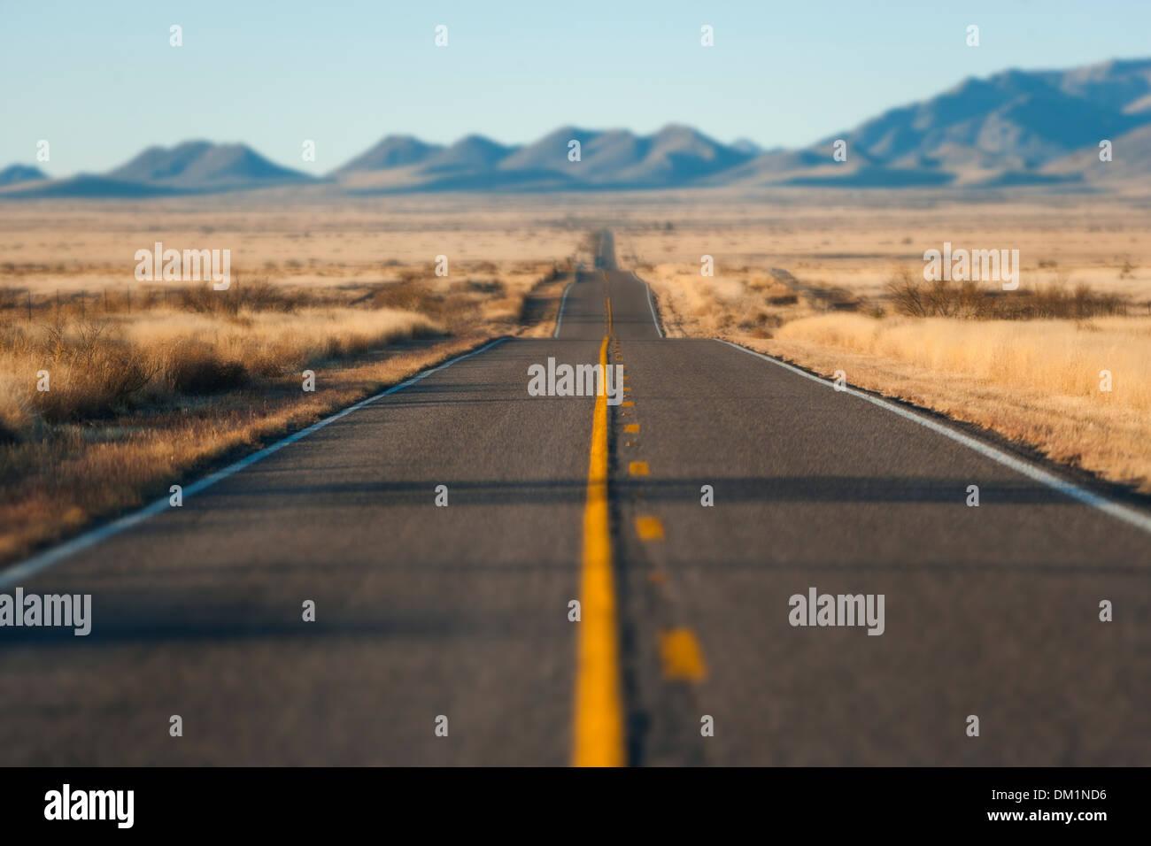 Une longue route à travers le désert de l'Arizona au coucher du soleil Photo Stock
