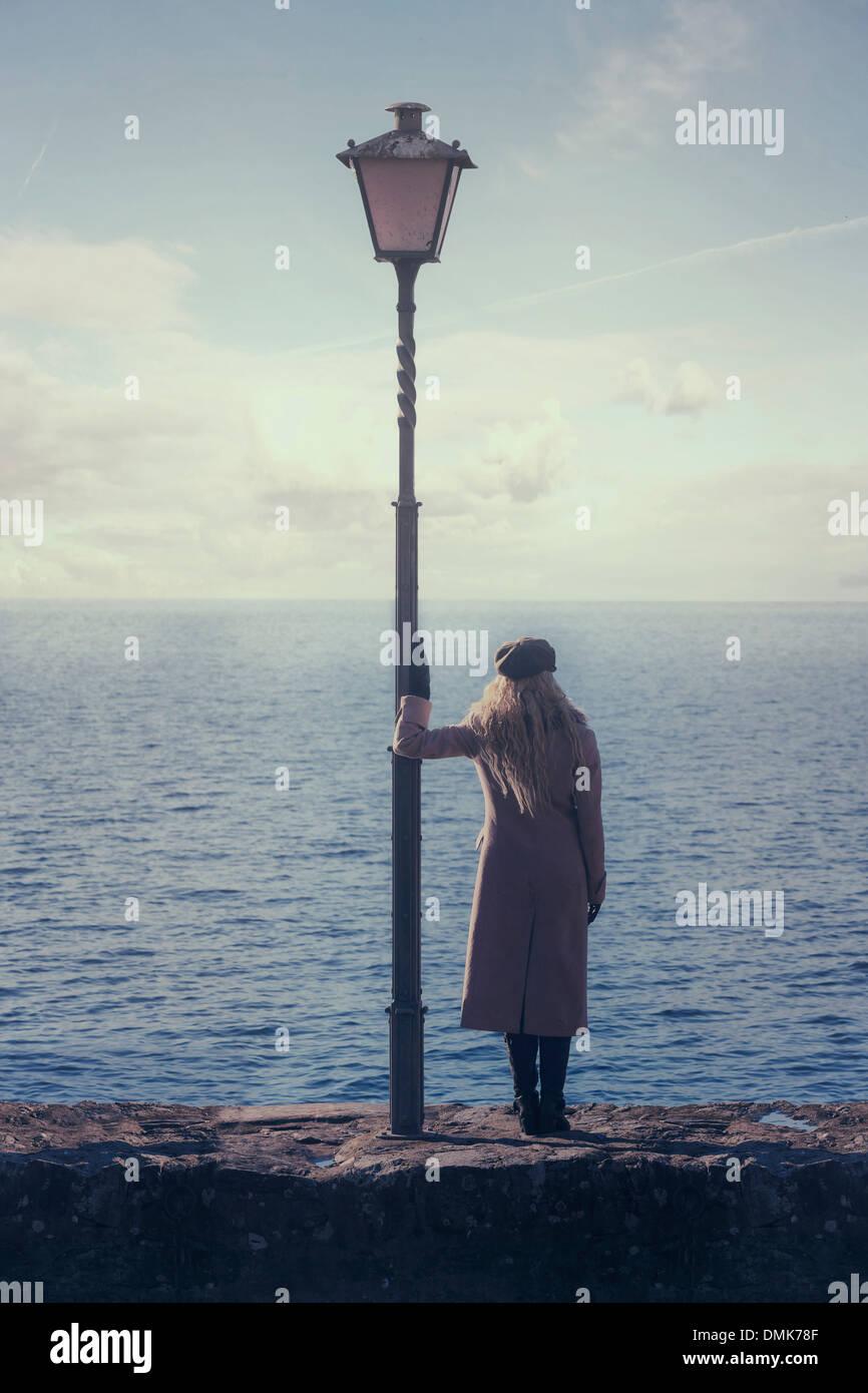 Une femme dans un manteau rose est debout à côté d'une lanterne à la mer Photo Stock