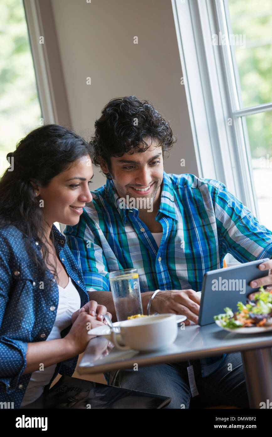 Un couple assis à la tablette numérique à un. Photo Stock