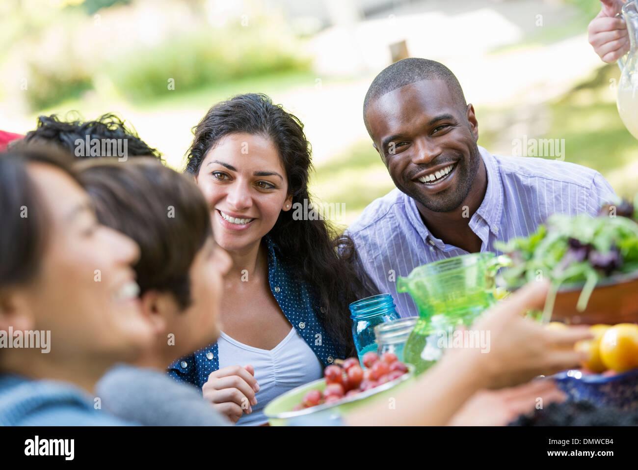 Les adultes et les enfants autour d'une table dans un jardin. Photo Stock