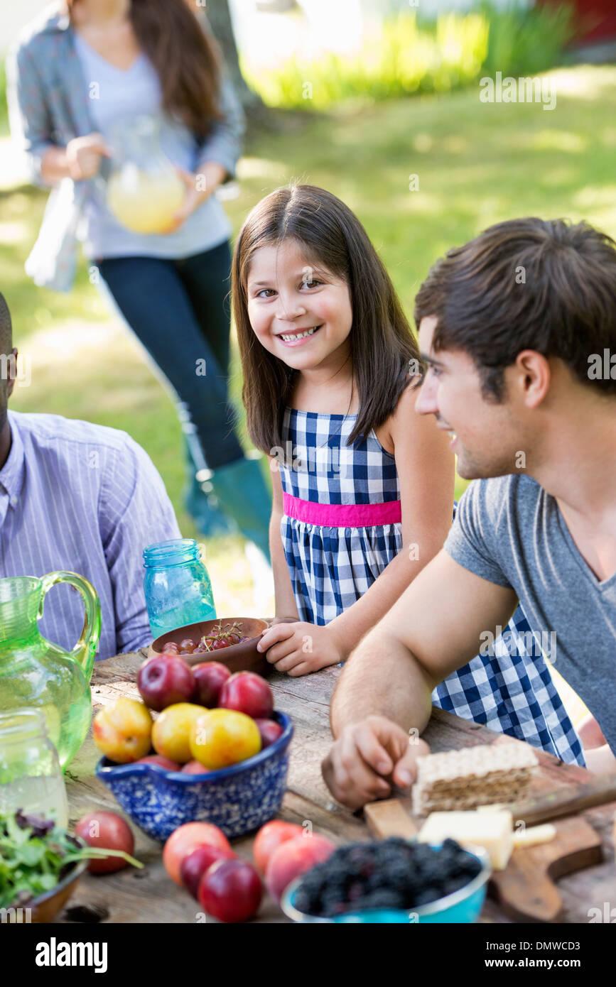 Les adultes et les enfants autour d'une table à une fête dans un jardin. Photo Stock