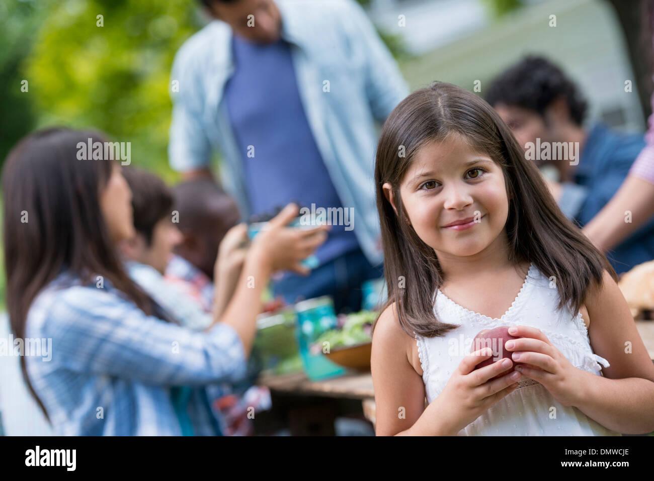 Une partie de l'été à l'extérieur. Les adultes et les enfants autour d'une table. Photo Stock