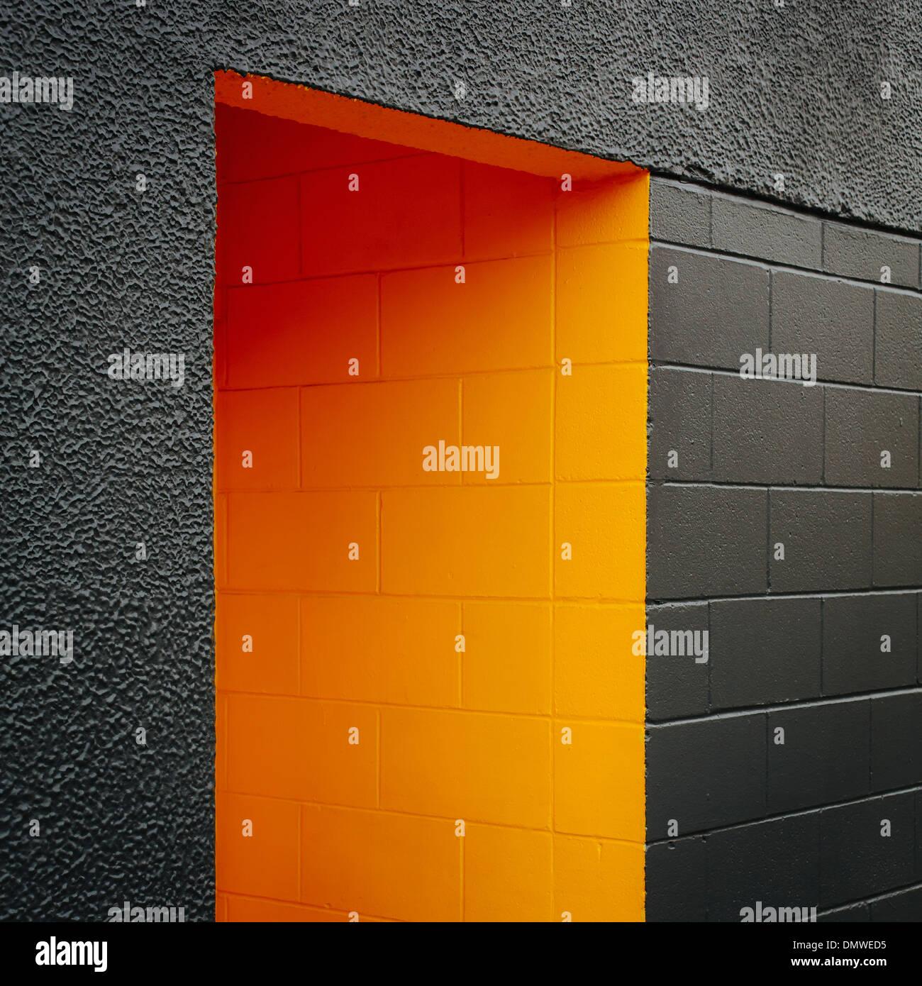 Une porte peinte en orange évidement un bloc gris mur de béton. Photo Stock