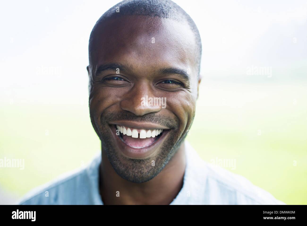 Un jeune homme en chemise bleue rire. Photo Stock