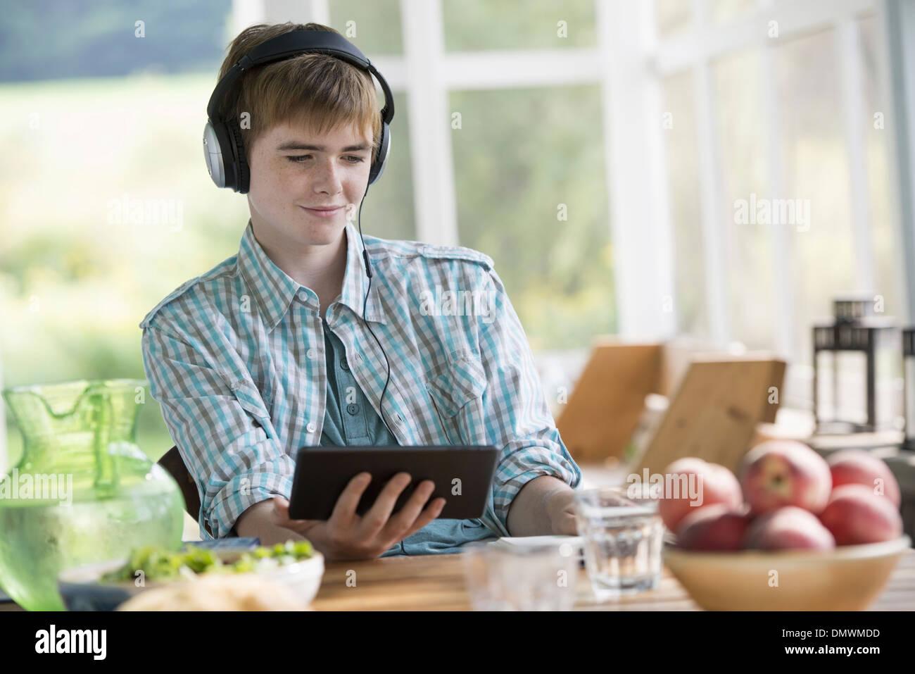 Un jeune garçon à l'écoute de la musique et à l'aide d'une tablette numérique. Banque D'Images