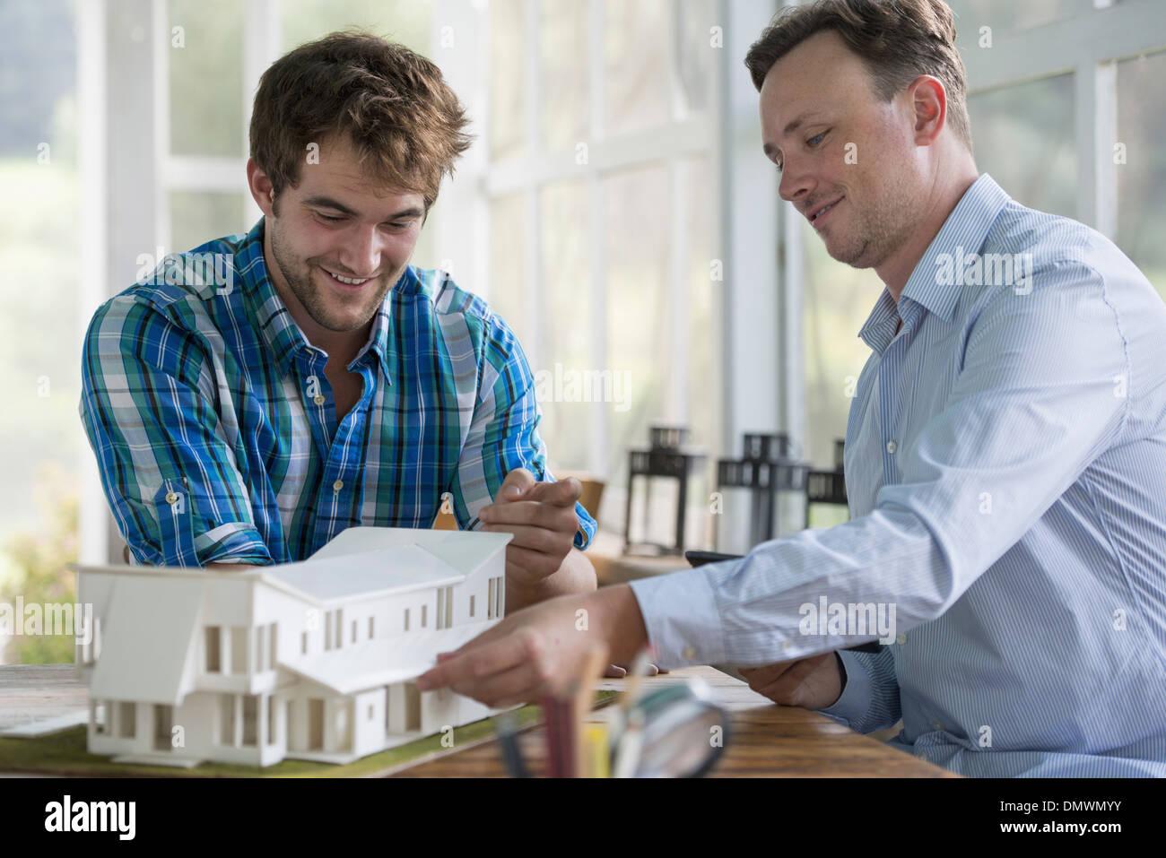 Deux hommes à la recherche d'un modèle d'architecture d'une maison. Photo Stock