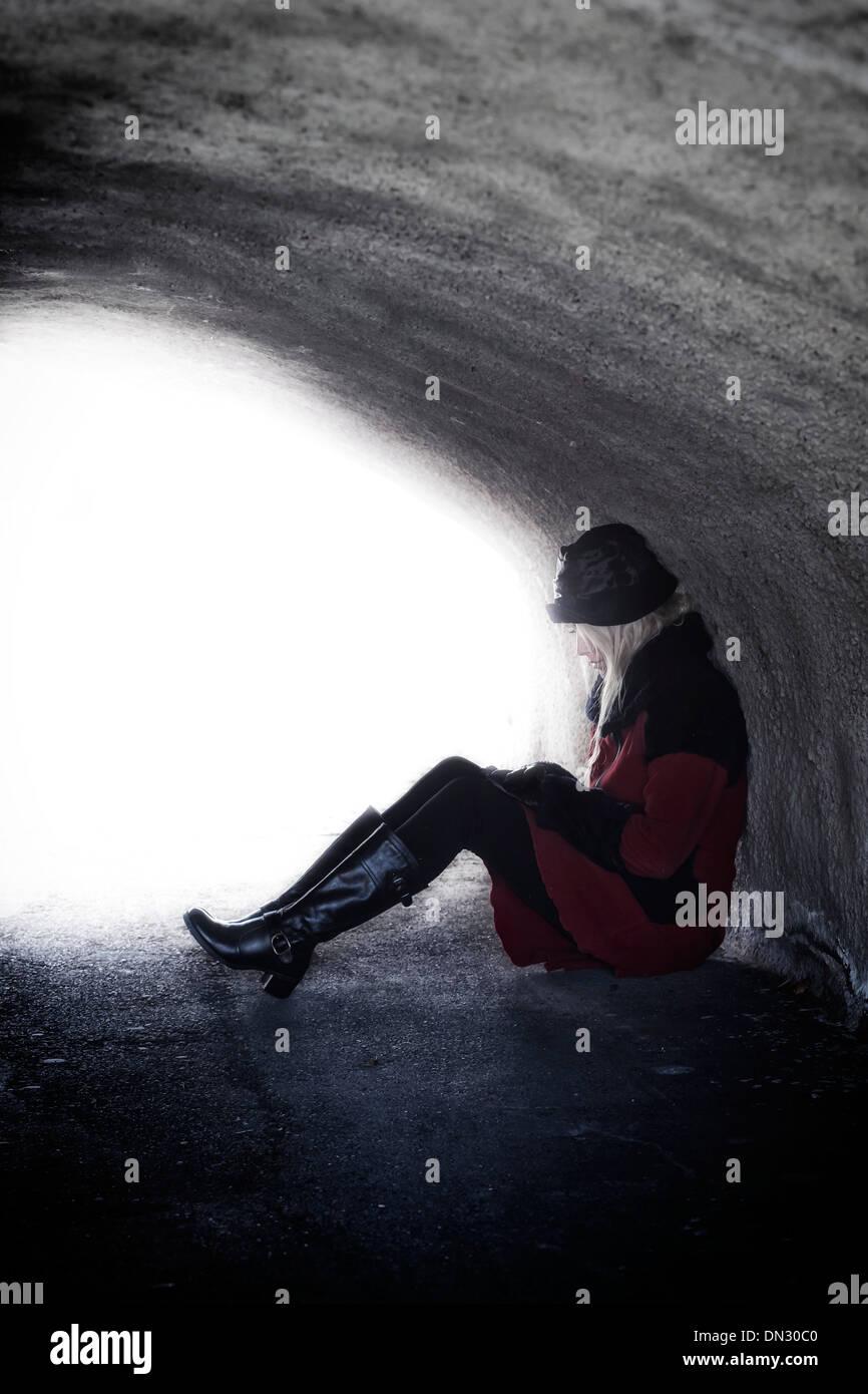 Une femme dans un manteau rouge est assis dans un tunnel noir Photo Stock
