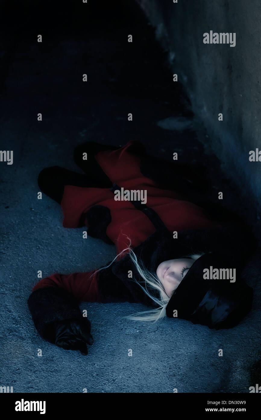 Une femme dans un manteau rouge est couché dans un tunnel noir Photo Stock