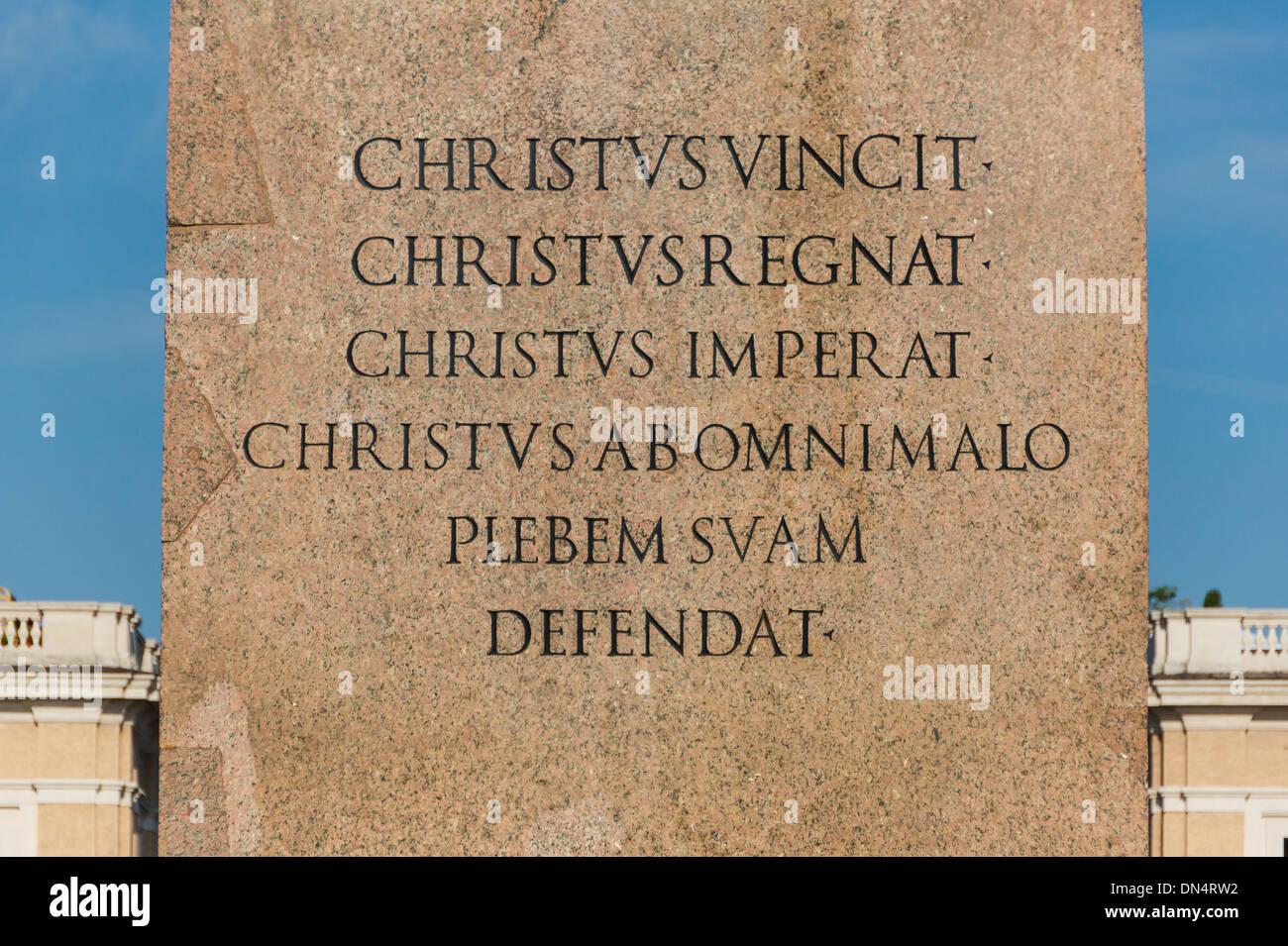 Texte latin chrétien sur le piédestal de l'obélisque à la place Saint Pierre, Vatican. Photo Stock