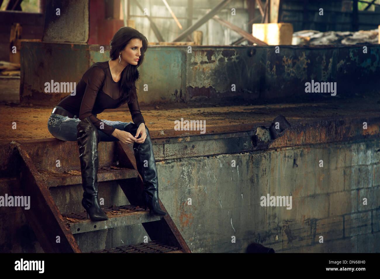 Femme assise sur un escalier intérieur rouillé entrepôt désaffecté Photo Stock