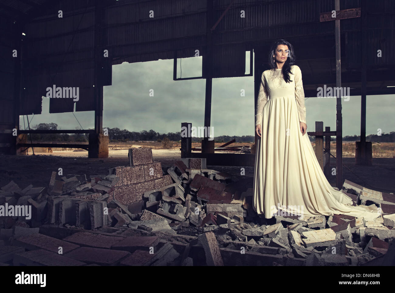 Femme en robe de mariage antique debout sur un tas de gravats Photo Stock
