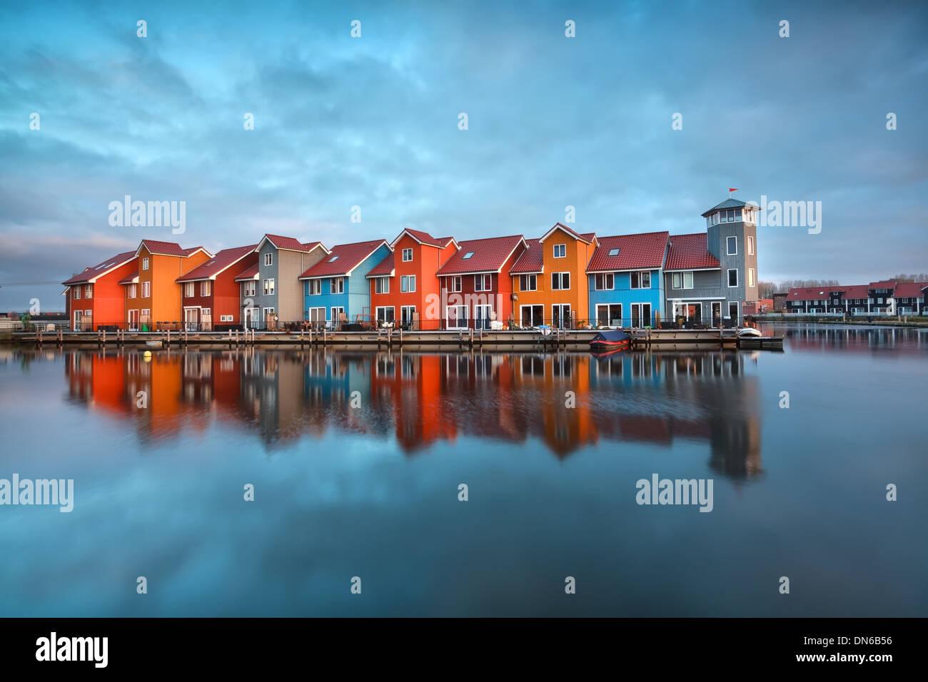 Bâtiments colorés sur l'eau au lever du soleil, Groningen, Pays-Bas Banque D'Images