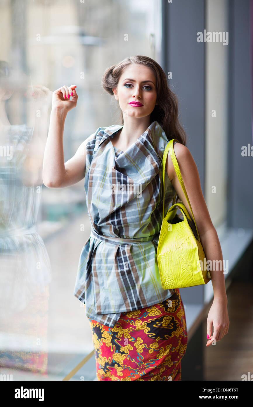 Une jeune fille brune portant un haut style tartan et floral jupe portefeuille avec un sac à main jaune. Photo Stock