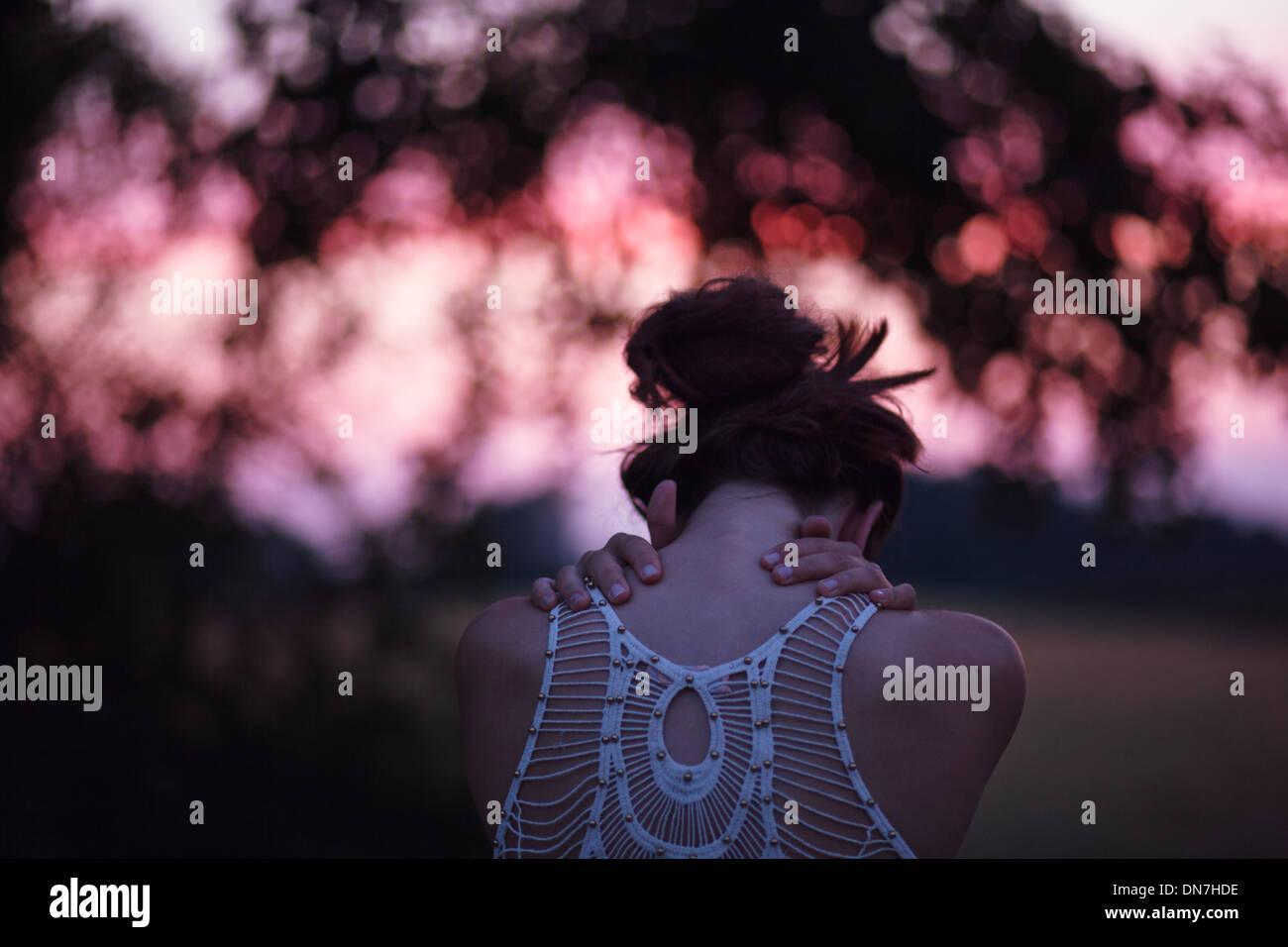 Vue arrière d'une jeune femme aux bras croisés Photo Stock