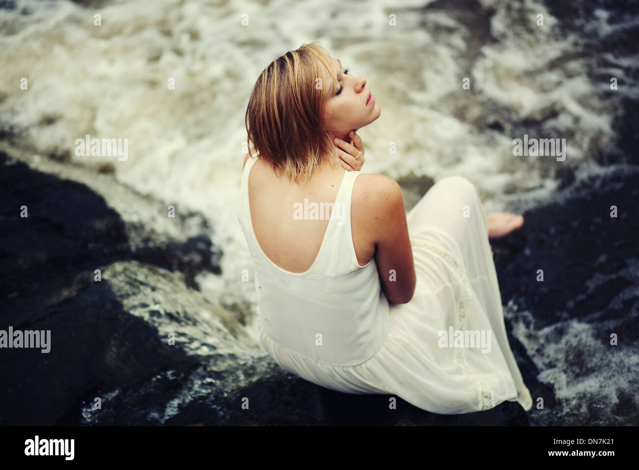 Jeune femme en robe blanche assise sur un creek Photo Stock