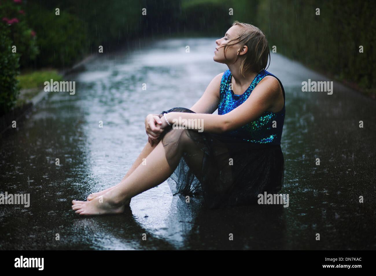 Jeune femme assise dans la pluie sur la route Photo Stock