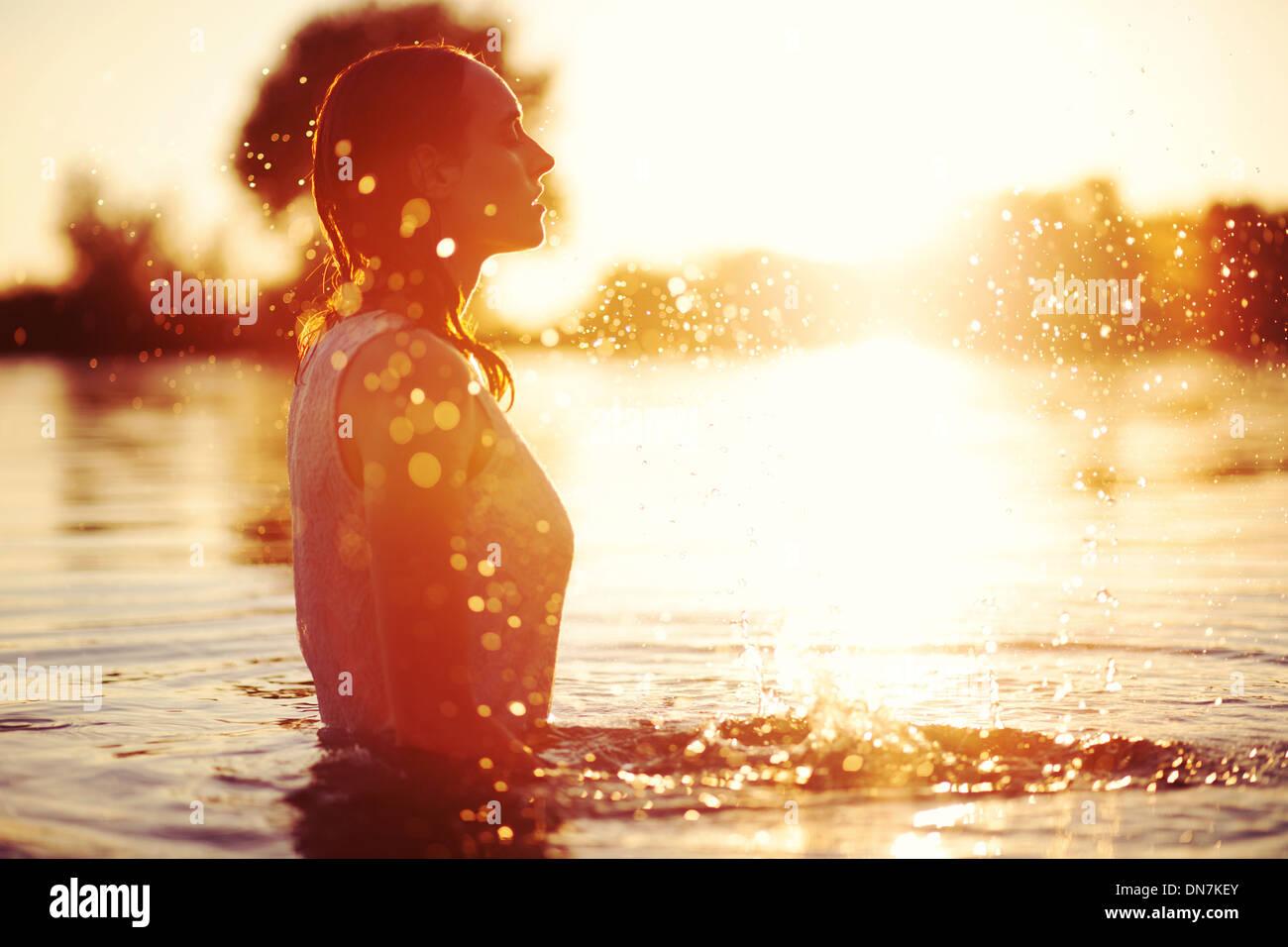 Jeune femme dans un lac au coucher du soleil avec de l'eau éclaboussant Photo Stock
