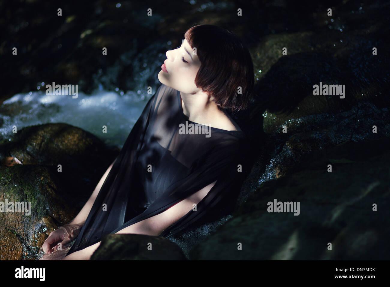 Jeune femme est assise sur un creek Photo Stock