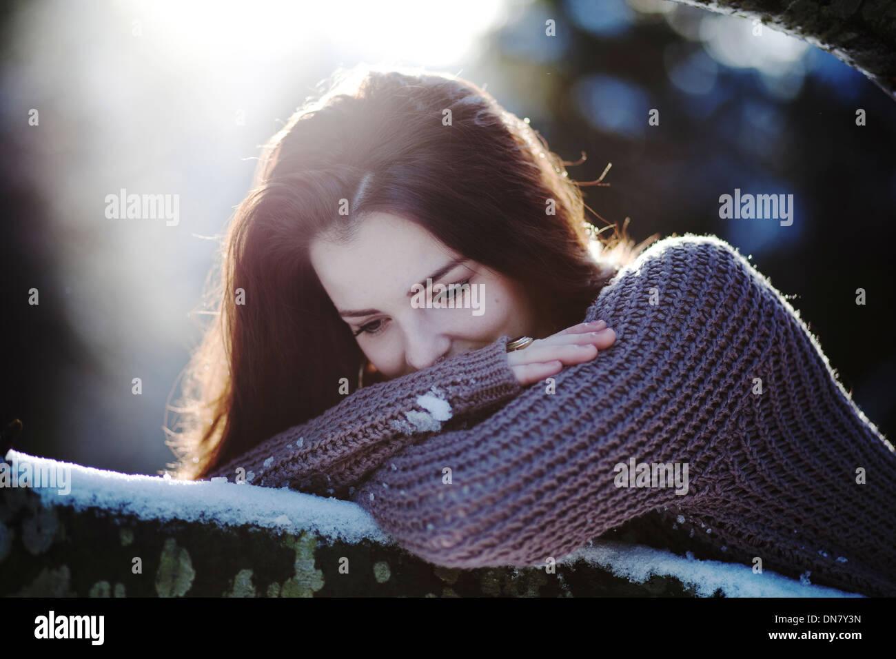 Jeune femme couchée sur un tronc d'arbre dans la neige Photo Stock