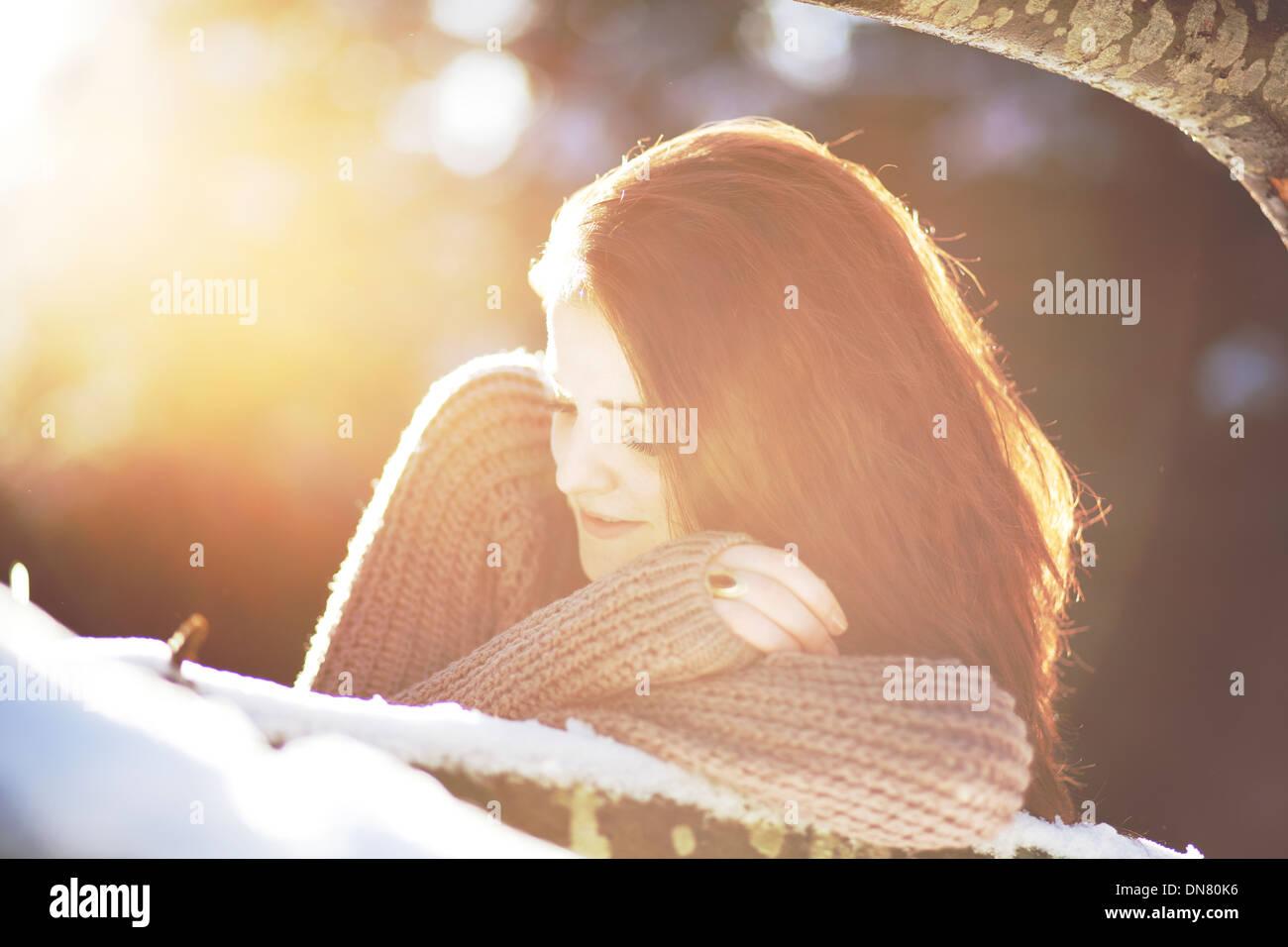Portrait d'une jeune femme dans la neige en rétro-éclairage Photo Stock
