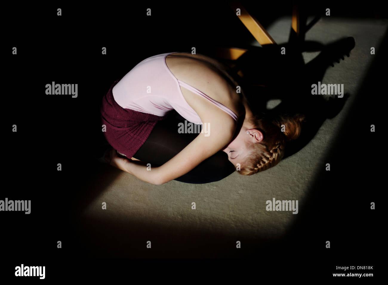 Jeune femme à genoux sur le sol, portrait Photo Stock