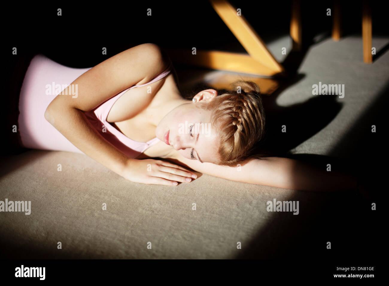 Jeune femme aux yeux clos se trouvant sur le plancher, portrait Banque D'Images