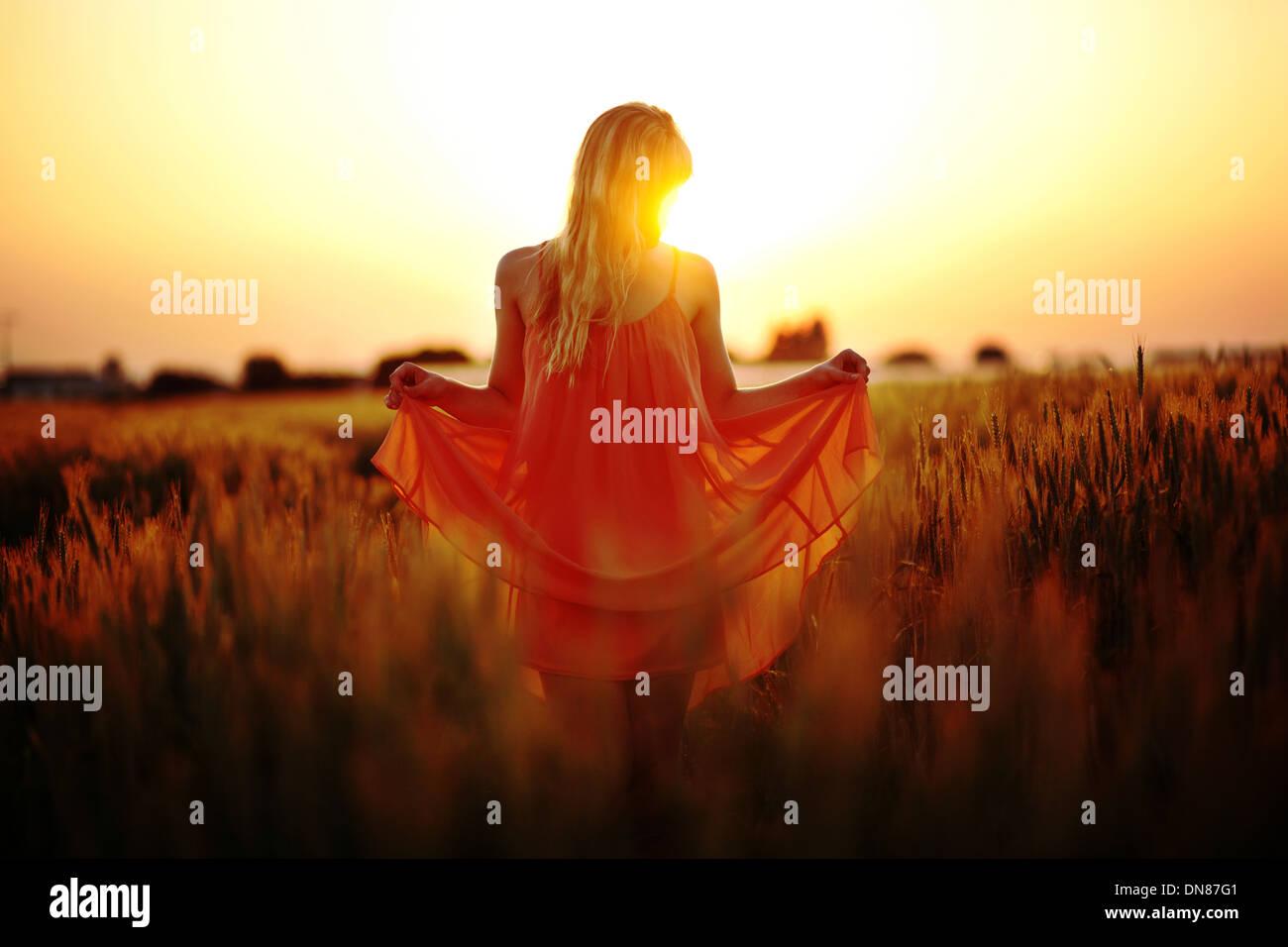 Robe femme debout dans le champ de blé au coucher du soleil Photo Stock
