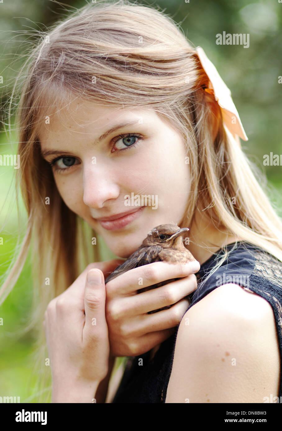 Fille avec jeune oiseau sur l'épaule Photo Stock