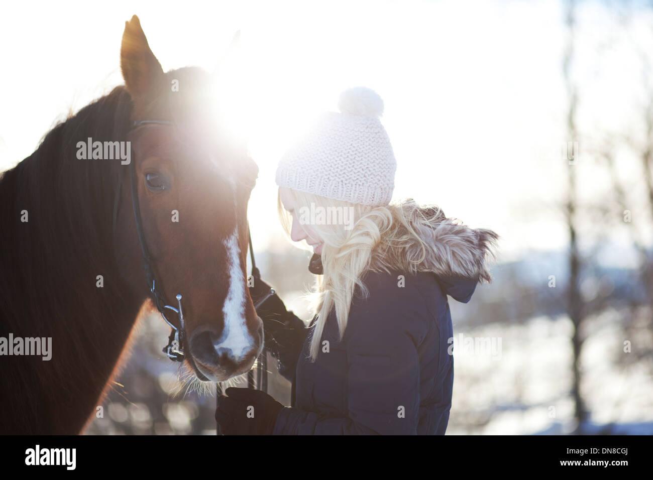 Jeune femme à cheval en hiver Photo Stock