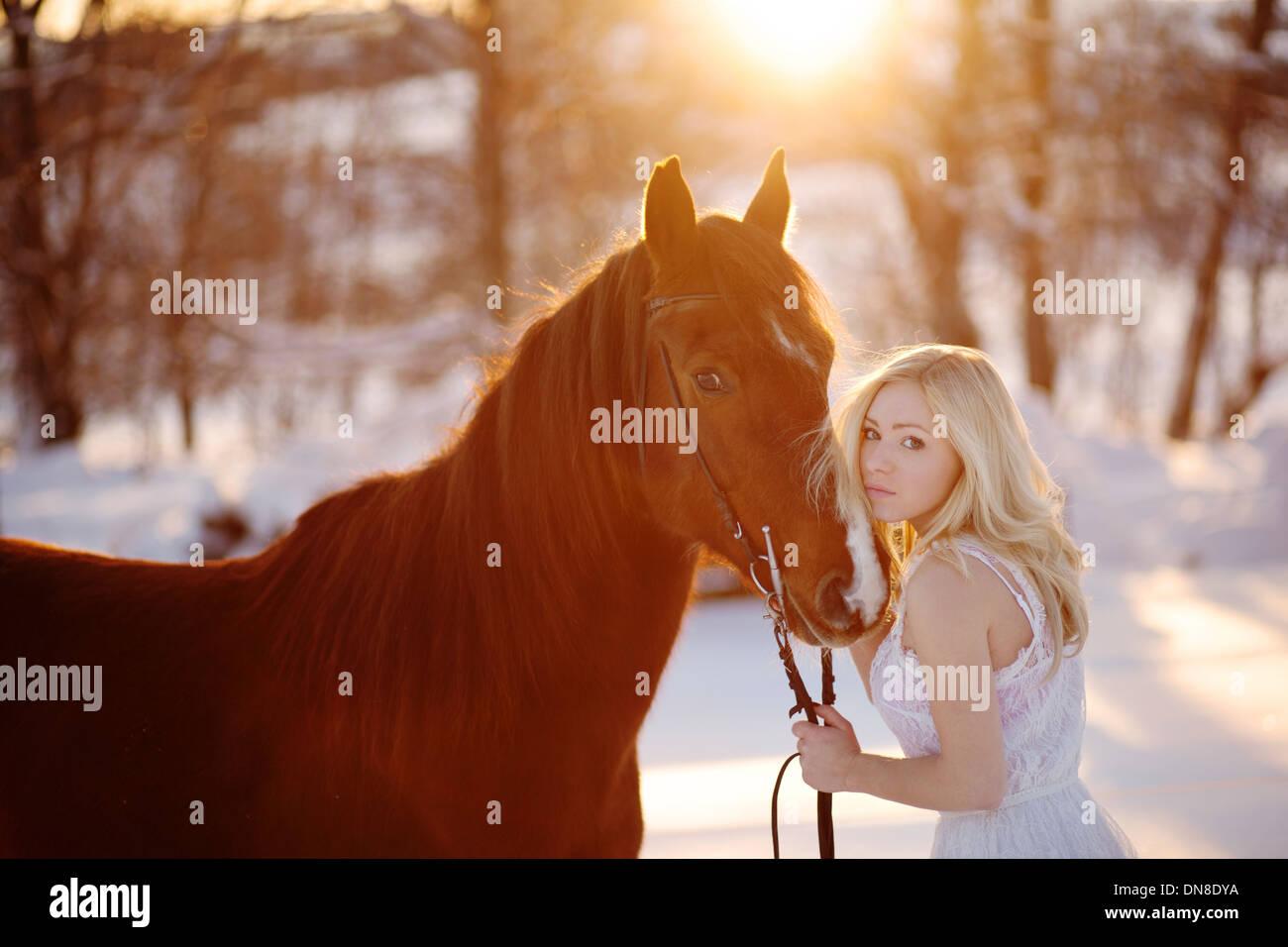 Jeune femme en robe blanche à cheval en hiver Photo Stock