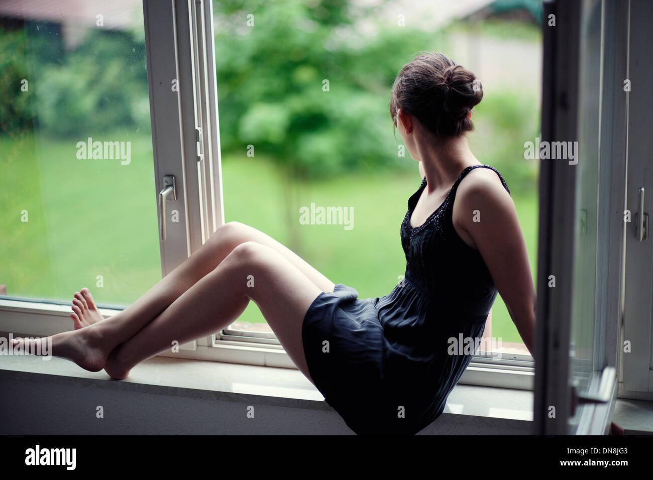 Jeune femme assise sur un rebord de fenêtre Photo Stock