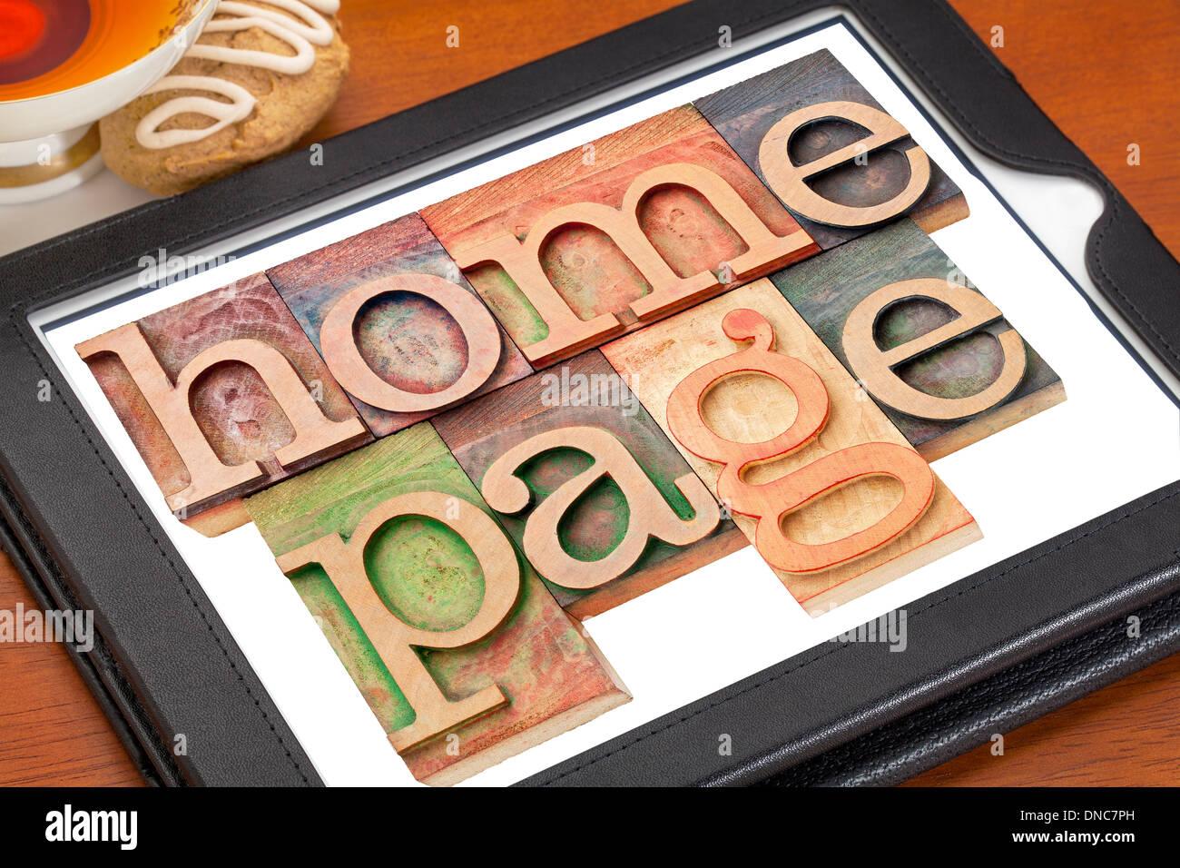 Home page - texte en typo bois type sur une tablette numérique avec tasse de thé Photo Stock