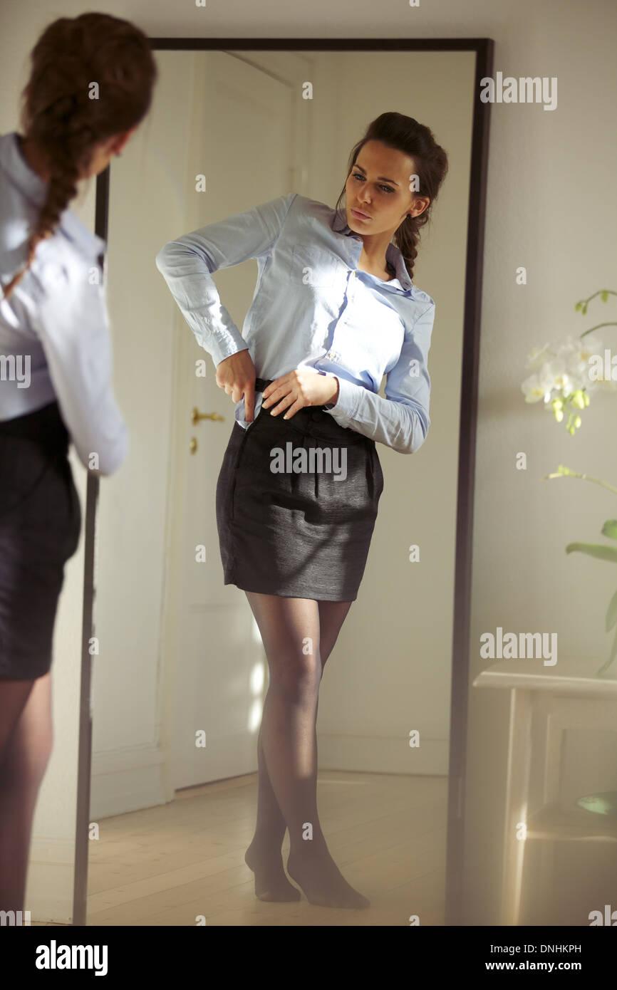 Belle jeune businesswoman fixant sa jupe en face du miroir. Pretty caucasian female model s'habiller. Photo Stock