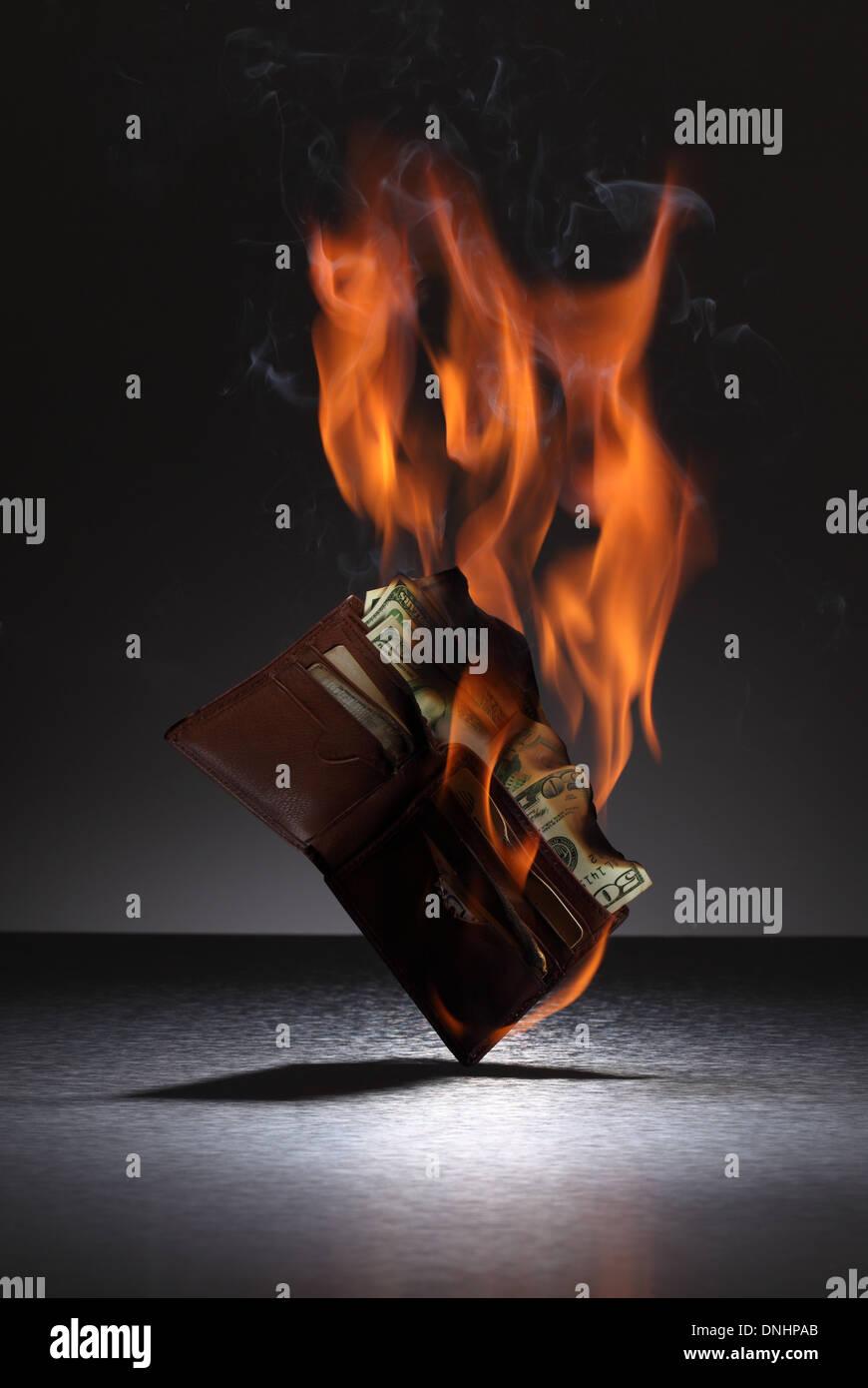 Un portefeuille en cuir brun rempli de cartes de crédit et de l'argent sur le feu. Photo Stock