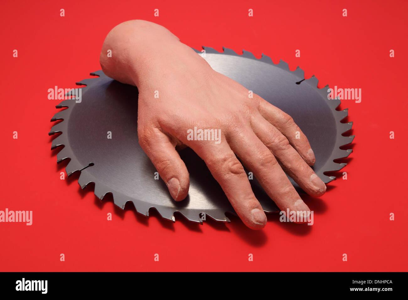 Une fausse main humaine sur une lame de scie circulaire en métal avec un fond rouge. Photo Stock