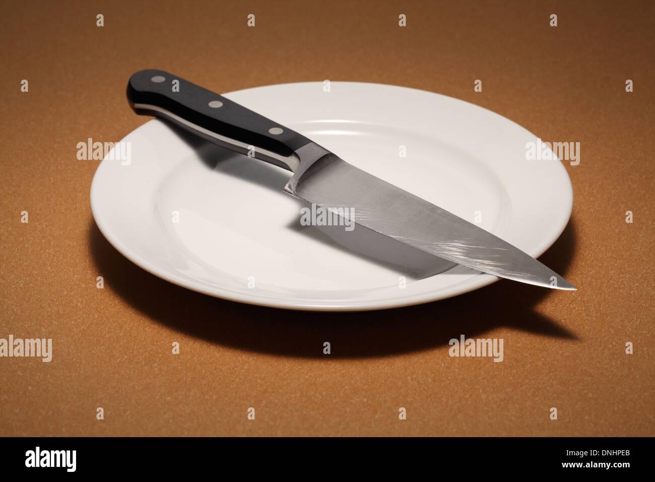 Un grand couteau de chef de cuisine sur une plaque manger blanche vide. Photo Stock