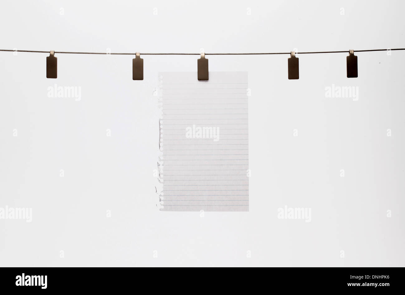 Une feuille de papier blanc accroché avec un clip à un fil droit. Fond blanc Photo Stock