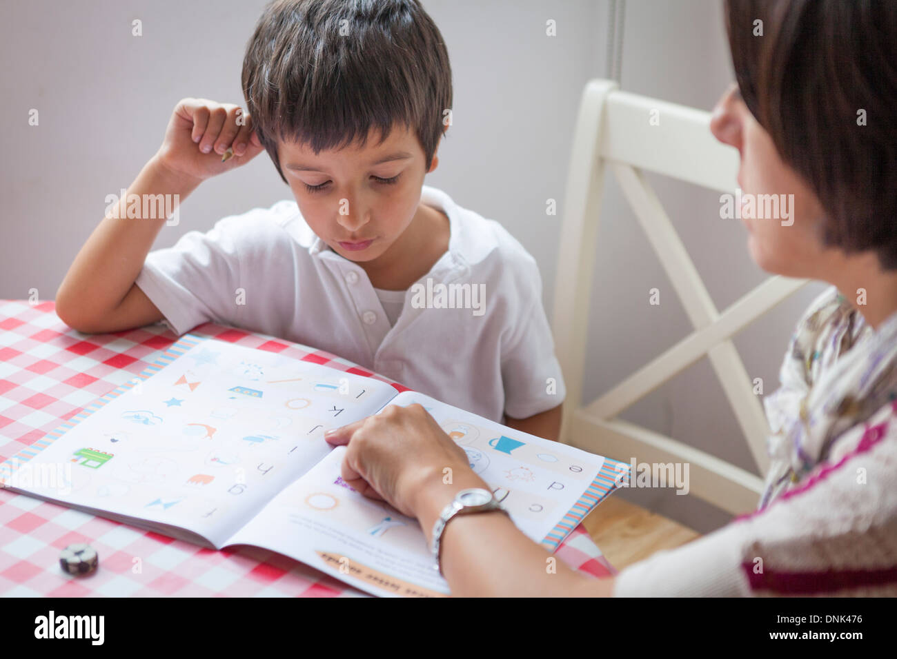 Mère d'aider un élève de primaire à faire leurs devoirs Photo Stock