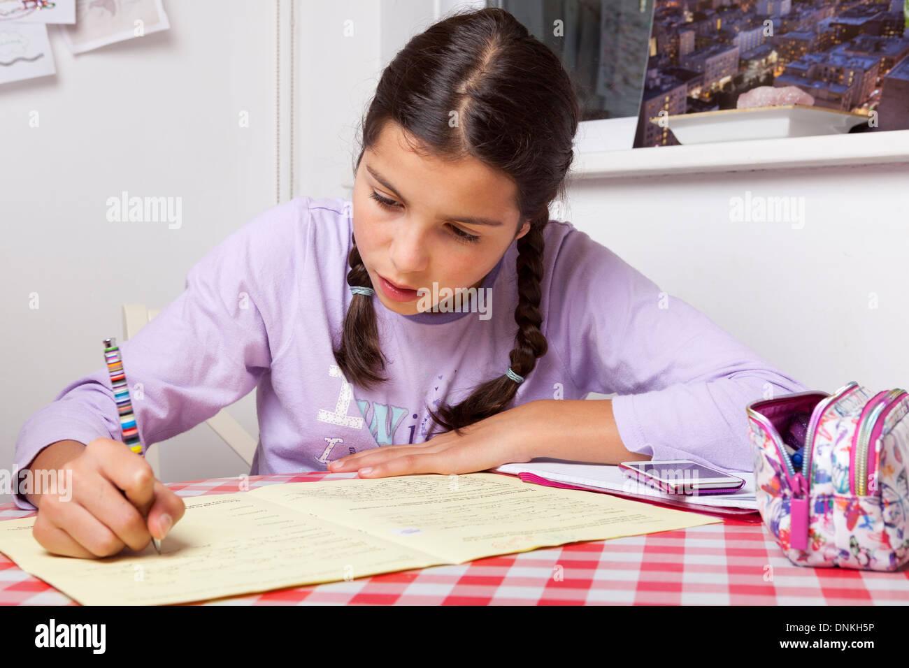 Travailler sur ses devoirs d'écolière Photo Stock