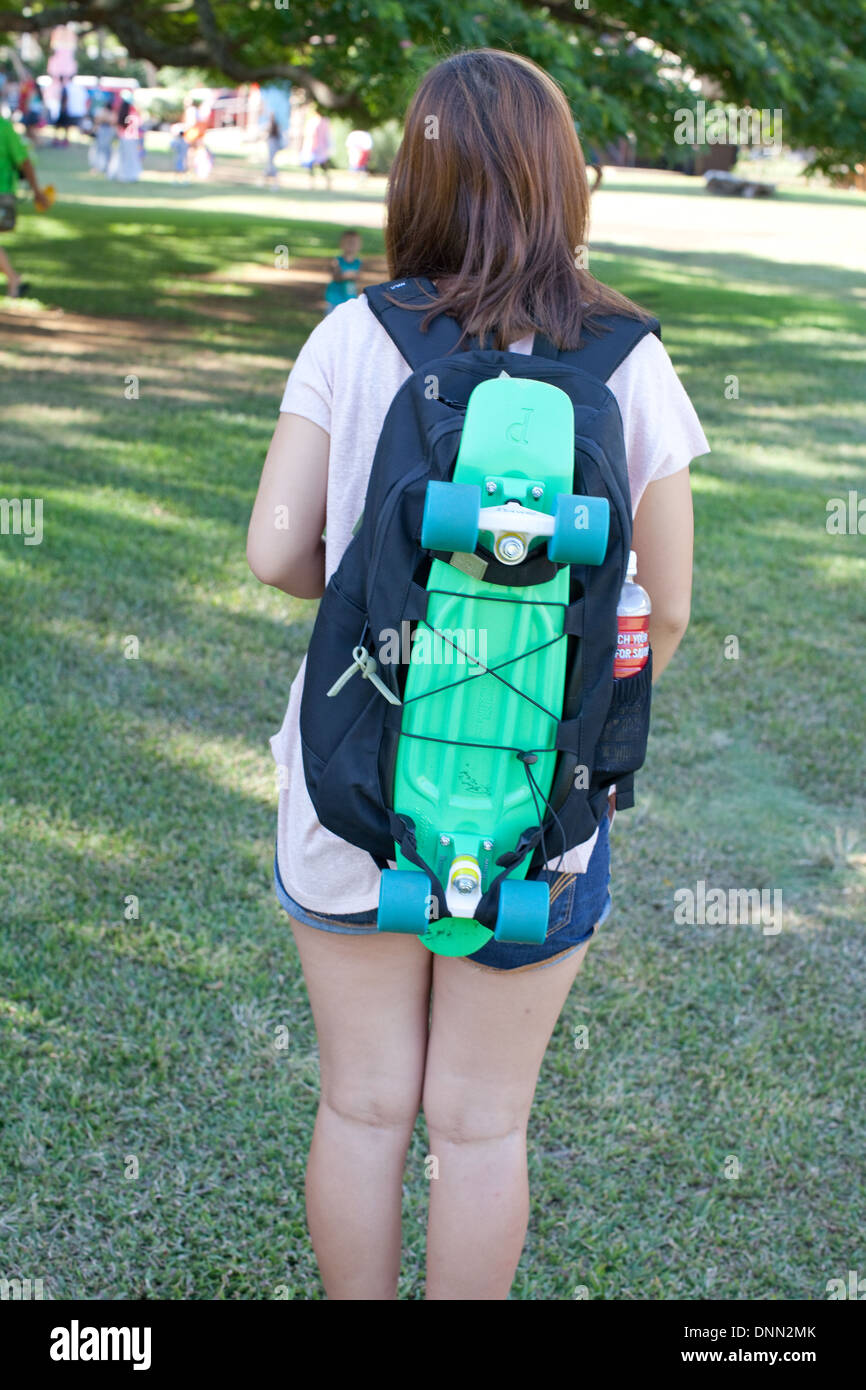 Teen portant un sac à dos à roulettes Banque D'Images