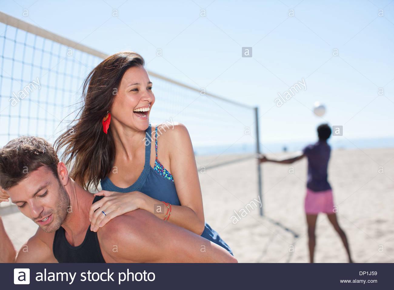 Man carrying girlfriend piggyback on beach Photo Stock