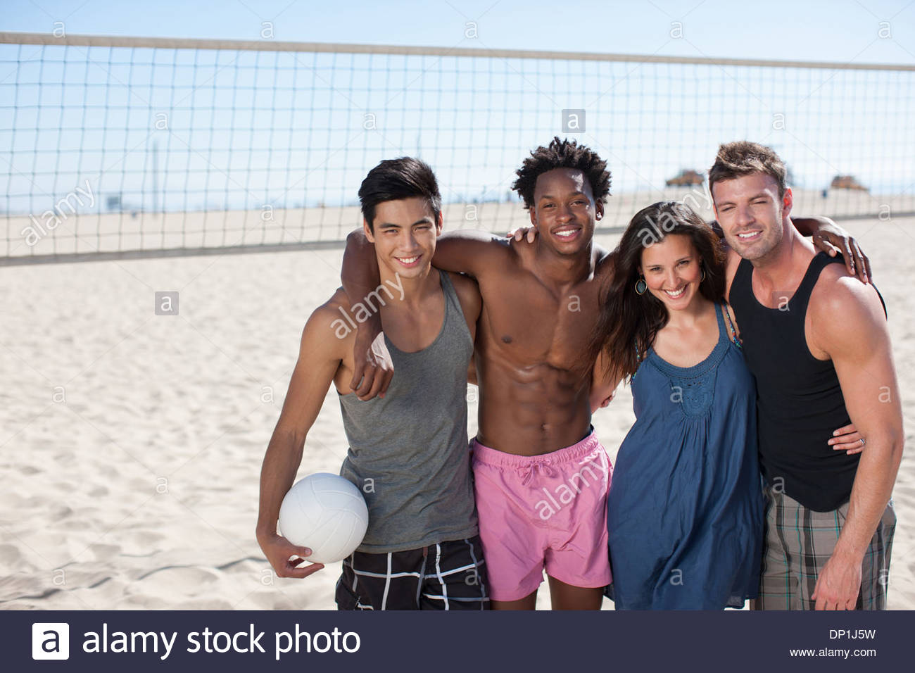 Quatre personnes debout sur le terrain de beach-volley Photo Stock