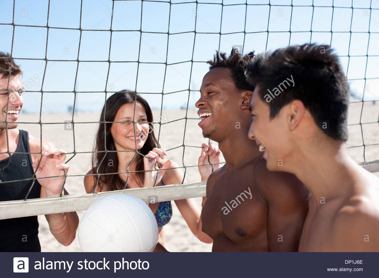 Quatre personnes debout sur le terrain de beach-volley Photo Stock