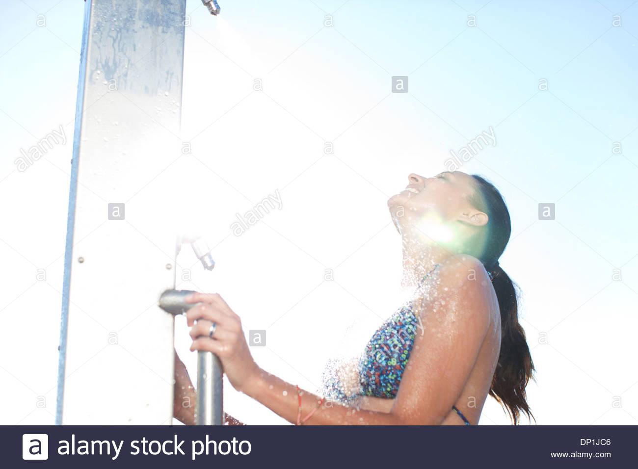Woman in bikini la douche on beach Photo Stock