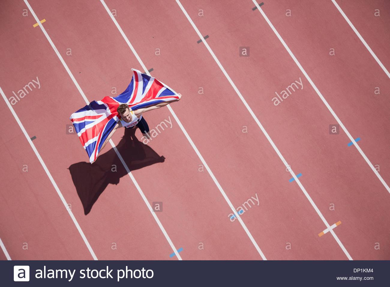 Runner célébrant avec drapeau britannique sur la voie Photo Stock